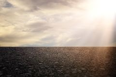 mörkt koncentrat- eller asfaltgolv med solnedgånghimmelbakgrund royaltyfria bilder