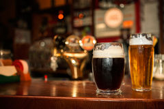 Mörkt och ljust öl i exponeringsglas arkivbild
