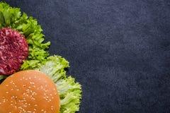 Mörkt restaurangmeny, hamburgareingredienser och kopieringsutrymme fotografering för bildbyråer