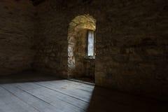 Mörkt rum med det stenväggar och fönstret Fotografering för Bildbyråer