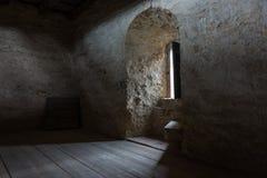 Mörkt rum med det stenväggar och fönstret Arkivbild