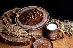 Mörkt sädes- bröd med solrosfrö, på en platta, sköll muttrar, kopp av mjölkar, begreppet av sunt äta, på en träbakgrundsnolla arkivfoton