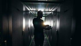 Mörkt serverrum med en manlig tekniker som fungerar en bärbar dator DET nätverkssäkerhetsbegrepp stock video