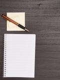 Mörkt skrivbord, spiralanteckningsbok, klibbiga anmärkningar, penna Arkivbilder