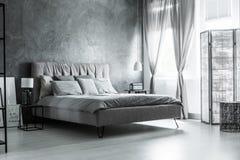 Mörkt sovrum med dekorativa gardiner royaltyfri foto