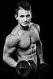 Mörkt svartvitt kontrastskott av den unga muskulösa armen för konditionmanmage hantlar som fungerar ut Arkivbilder