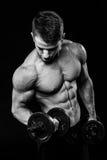 Mörkt svartvitt kontrastskott av den unga muskulösa armen för konditionmanmage hantlar som fungerar ut Royaltyfri Bild