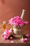Mörser mit rosafarbenen Blumen für Aromatherapie und Badekurort Stockfotos