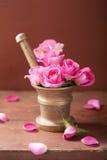Mörser mit rosafarbenen Blumen für Aromatherapie und Badekurort Stockbild