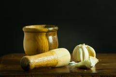 Mörser und Stampfe mit Knoblauch auf einem Holztisch stockfotos