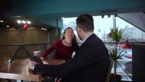Möta en ung flicka och en grabb i en kaféflicka som ser intresserad i en grabbminnestavla lager videofilmer