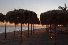 Möte av en ny dag på gryning på kusten av ett lugna hav i sanden Royaltyfria Bilder