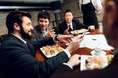 Möte av japanska affärsmän i restaurang Män äter sushi och samtal royaltyfri fotografi