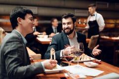 Möte av kinesiska affärsmän i restaurang Två män äter sushi arkivbild