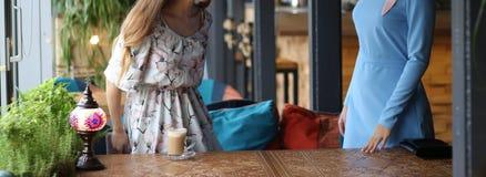 möte av två kvinnor i ett kafé för kaffe en som upp till stås, hälsar andra den blåa klänningen, klänning i blomma, på den sned t royaltyfri fotografi