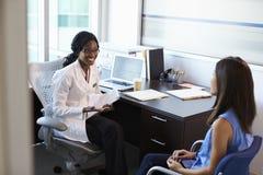 Möte för doktor Wearing White Coat med den kvinnliga patienten royaltyfria bilder