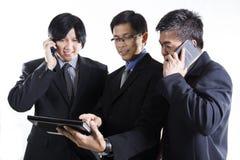 Möte för tre affärsman och användamobiltelefon Arkivfoton