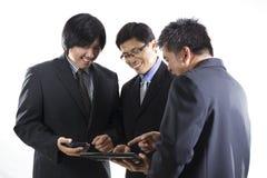 Möte för tre affärsman och användamobiltelefon Royaltyfri Fotografi