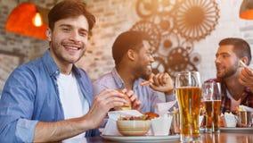 Möte i bar Vänner som äter hamburgare och dricker öl royaltyfria bilder