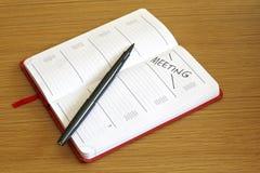 Möte som bokas in i dagboken arkivbild
