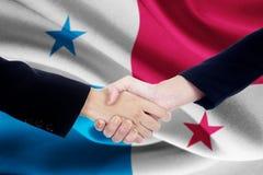 Mötehandskakning med flaggan av Panama Arkivfoton