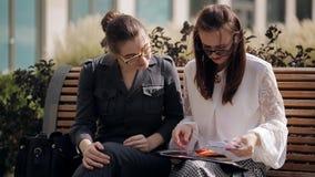 Mötet av två affärskvinnor near affärsmitten Möte och diskussion av affärskvinnorna för transaktion två arkivfilmer