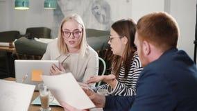 Mötet för affärsstarten i ett arkitektoniskt modernt kontor skissar planläggning lyckliga ungdomarsom är involverade i konversati stock video