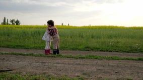 Mötevänner, gulliga barn som kramar sig spring runt om fältvägen, ultrarapid, pojken och flickan är det lyckliga mötet, arkivfilmer