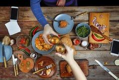 Mötevänner på matställetabellen med amerikanskt mellanmål och vin Upp av exponeringsglas av vinrostat bröd Arkivfoton