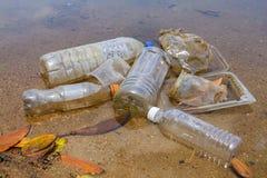 Mún hábito ambiental de la disposición incorrecta de las tazas no-biodegradables y de las botellas del PVC en un lago Foco select imagen de archivo