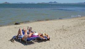 Múrcia, Espanha - 22 de junho de 2019: Pares felizes que leem um livro e que relaxam na praia durante um dia de verão ensolarado fotos de stock