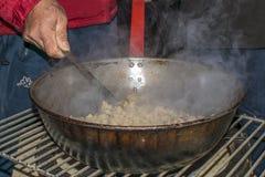 Múrcia, Espanha, o 18 de abril de 2019: Homem que cozinha os migas ou as migalhas, um alimento espanhol típico em uma frigideir imagens de stock royalty free