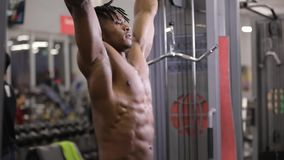 Músculo de bombeo del ABS del hombre afroamericano que cuelga en barra horizontal en gimnasio almacen de metraje de vídeo
