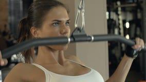 Músculo del entrenamiento de la mujer de la aptitud del retrato en el equipo de deportes moderno en club del gimnasio almacen de metraje de vídeo