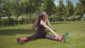 Músculos asiáticos del entrenamiento de la mujer que se sientan en césped del parque almacen de video