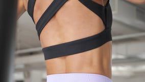Músculos en la parte de atrás de una mujer que levanta en la barra en gimnasio almacen de video