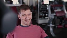 Músculos pectorales de los trenes atléticos y atractivos del hombre en un simulador en el gimnasio almacen de video
