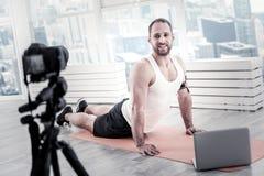 Músculos relajantes del vientre del blogger masculino atractivo Foto de archivo libre de regalías