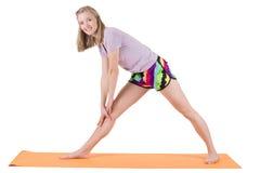 Músculos rubios hermosos del entrenamiento de la mujer de la parte posterior y de las piernas en una estera Imagen de archivo libre de regalías