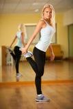 Músculos strerching de la mujer apta después del entrenamiento en gimnasio Foto de archivo