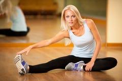 Músculos strerching de la mujer apta después del entrenamiento en gimnasio Fotos de archivo