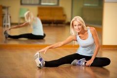 Músculos strerching de la mujer apta después del entrenamiento en gimnasio Fotos de archivo libres de regalías