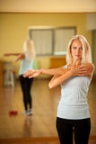 Músculos strerching de la mujer apta después del entrenamiento en gimnasio Imágenes de archivo libres de regalías