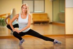 Músculos strerching de la mujer apta después del entrenamiento en gimnasio Imagen de archivo libre de regalías
