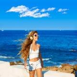 Música adolescente de los auriculares de la muchacha del niño rubio en la playa Imagen de archivo libre de regalías