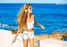 Música adolescente de los auriculares de la muchacha del niño rubio en la playa Fotos de archivo