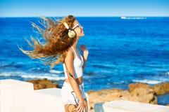Música adolescente de los auriculares de la muchacha del niño rubio en la playa Imagen de archivo
