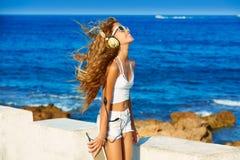Música adolescente de los auriculares de la muchacha del niño rubio en la playa Foto de archivo