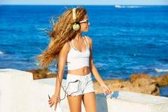 Música adolescente de los auriculares de la muchacha del niño rubio en la playa Imágenes de archivo libres de regalías