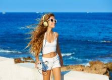 Música adolescente de los auriculares de la muchacha del niño rubio en la playa Foto de archivo libre de regalías